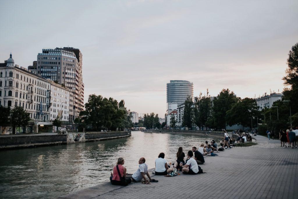 Menschen abends am Donaukanal. sitzend